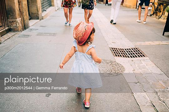 France, Aix-en-Provence, toddler girl walking down the streets of the city center - p300m2012544 von Gemma Ferrando