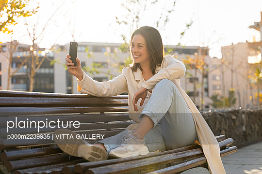 Smiling businesswoman talking selfie through smart phone while sitting on bench - p300m2239935 by VITTA GALLERY