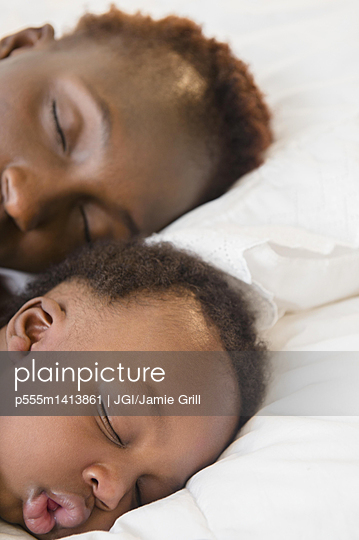 Black mother and son sleeping on bed - p555m1413861 by JGI/Jamie Grill