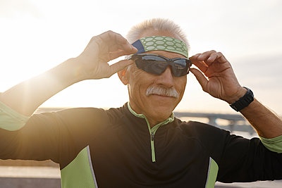 Sporty Senior Man Putting On Sunglasses - p1166m2147027 by Cavan Images