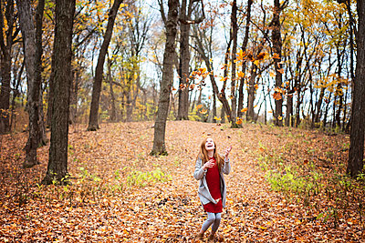 Young Red Hair Girl Playing Outside in Fall Leaves - p1166m2147063 by Cavan Images