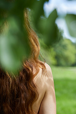 back of long haired redhead woman in nature - p1540m2291472 by Marie Tercafs