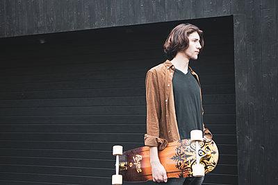 Junger Mann mit Skateboard - p1640m2295993 von Holly&John