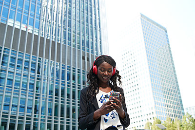 Businesswoman wearing headphones using mobile phone while standing in city - p300m2241624 by Pete Muller