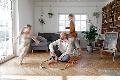 Siblings running around father sitting on floor in living room at home - p300m2275623 by Katharina Mikhrin