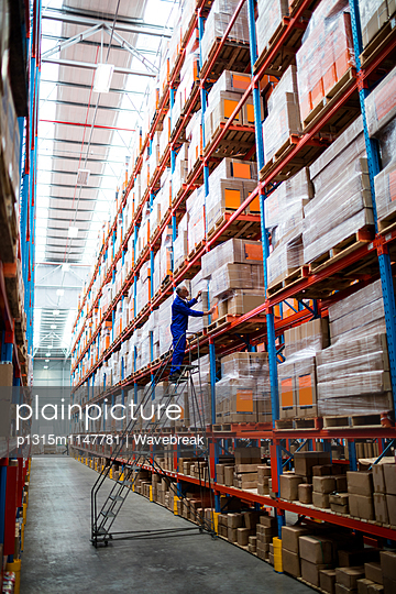 Man worker checking a pallet on the stairs in warehouse - p1315m1147781 by Wavebreak