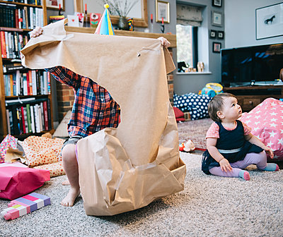 A boy unwrapping presents at a birthday party. - p1100m1158509 by Mint Images