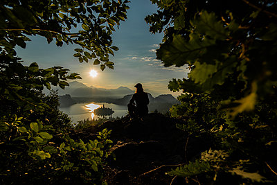 Person watching an early morning sunrise at Lake Bled - p1455m2043696 by Ingmar Wein