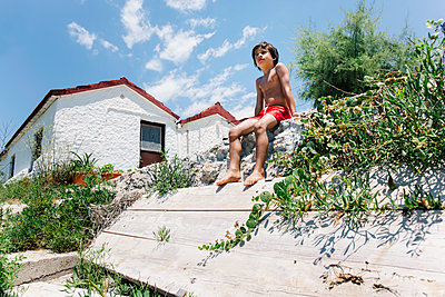 Boy sitting in swimming trunks in sunshine in front of a house - p300m2041749 by Nasos Zovoilis