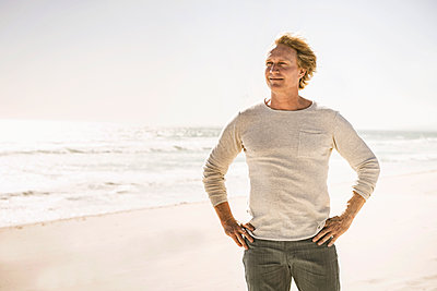 Portrait of smiling man standing on the beach - p300m2167076 by Floco Images