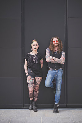 Portrait of punk hippy couple leaning against wall - p429m1013725f by Eugenio Marongiu