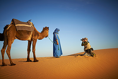 Tourist photographing guide with camel on sand dune in desert landscape - p555m1415062 by LWA/Larry Williams