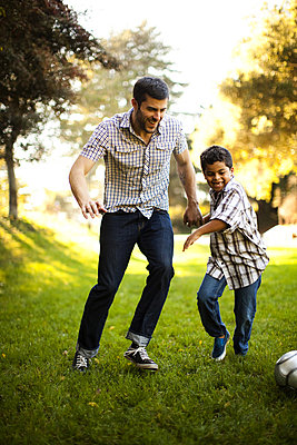 Father and son playing soccer together - p924m757031f by Wonwoo Lee