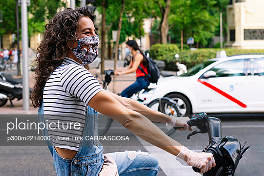 Happy woman riding sharing electric bicycle on street in city during pandemic - p300m2214000 by Jose Luis CARRASCOSA