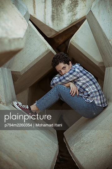 Sad young woman sitting on concrete blocks looking away  - p794m2260354 by Mohamad Itani