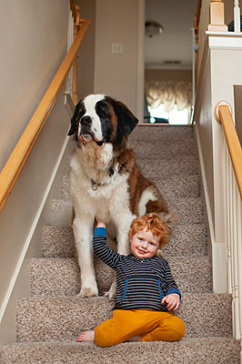 Toddler boy smiling and leaning on large dog at home on the stairs - p1166m2137305 by Cavan Images