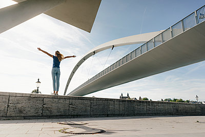 Netherlands, Maastricht, young woman standing on a wall at a bridge - p300m2058803 by Gustafsson