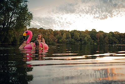 Friends having fun on a lake on a pink flamingo floating tire - p300m2114297 by Gustafsson