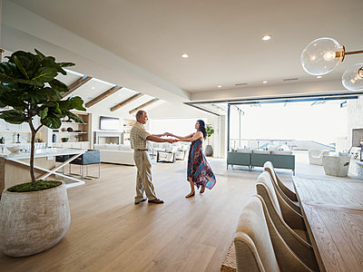 Older couple dancing in modern home - p555m1491039 by Erik Isakson