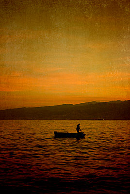 Man in fishing boat at sunrise - p7940550 by Mohamad Itani