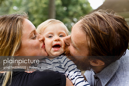Mother and father kissing baby girl on cheek, outdoors - p1427m2283222 by Roberto Westbrook