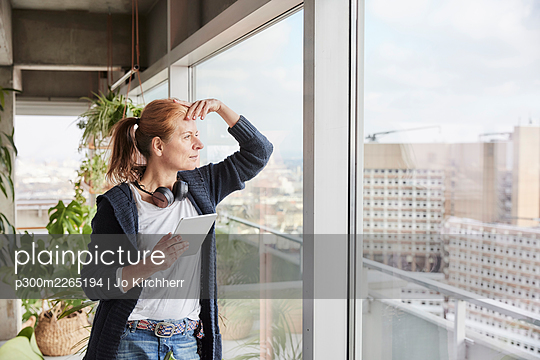 Woman with headphones holding digital tablet while looking through window - p300m2265194 by Jo Kirchherr