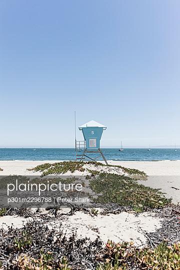 Lifeguard hut on sunny blue sky ocean beach, Santa Barbara, California - p301m2296788 by Peter Stark