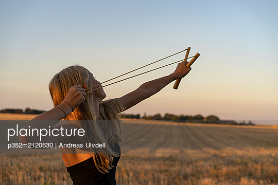 Teenage girl using sling shot in field - p352m2120630 by Andreas Ulvdell