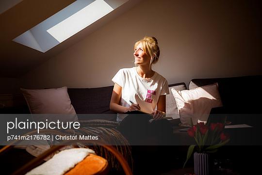Junge Frau am Dachfenster im Sonnenschein - p741m2176782 von Christof Mattes