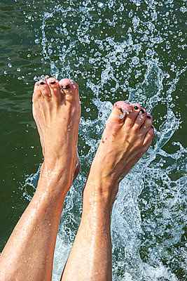 Woman splashing her feet in water - p1418m1589544 by Jan Håkan Dahlström