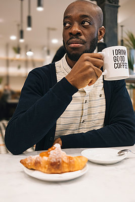 Man with croissant and cup of coffee in a cafe looking around - p300m1568262 von Mauro Grigollo