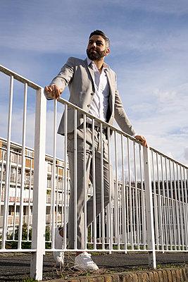 Male professional standing on footbridge at railing  - p300m2275132 by Francesco Buttitta