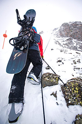 A snowboarder climbs a steep section of a mountain. - p343m1184689 by Rob Hammer