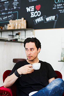 Mid adult man looking away while having coffee at cafe - p426m958764f by Astrakan