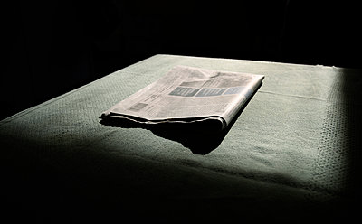 A newspaper folded, waiting to be read in morning light, low key - p924m2127203 by Mischa Keijser