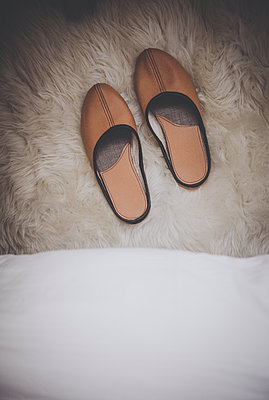 Pair of leather slippers next to bed  - p970m1425974 by Katya Evdokimova