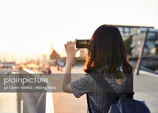 Asiatin macht ein Foto mit Smartphone - p1124m1169903 von Willing-Holtz