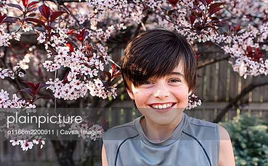 Portrait of happy young boy in front of flowering trees in a garden. - p1166m2200911 by Cavan Images