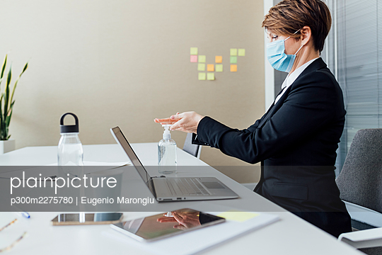 Female entrepreneur with protective face mask using hand sanitizer while sitting at desk - p300m2275780 by Eugenio Marongiu