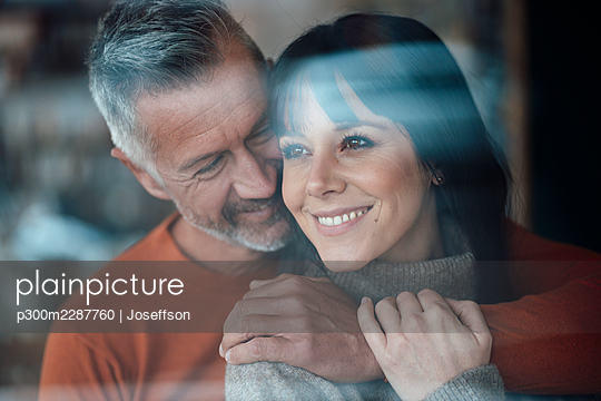 Mature man with arm around on woman smiling at cafe - p300m2287760 by Joseffson