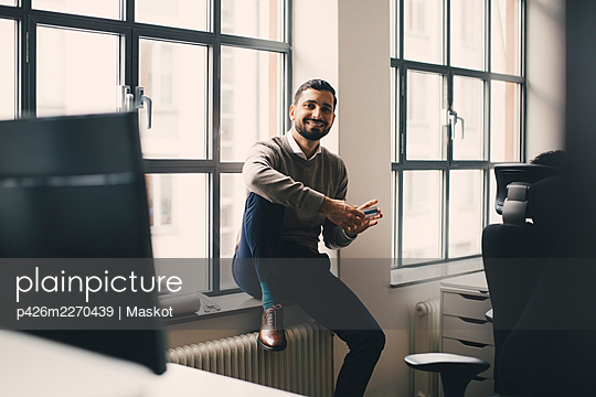 Portrait of smiling businessman with box sitting against window in creative office - p426m2270439 by Maskot