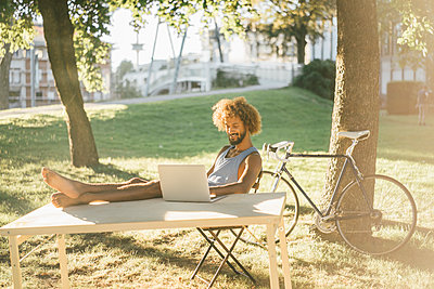 Man with beard and curly hair using laptop at table in park - p300m1470143 by Kniel Synnatzschke