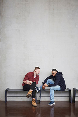 Full length of happy male students with technologies sitting on bench against wall in university - p426m2022759 by Maskot