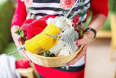 Midsection of senior woman holding knitting basket at nursing home - p426m977480f by Maskot