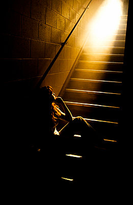 Depressed girl in stairwell with light streaming in - p4424745f by Design Pics