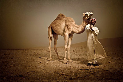 Beduin holding a camel in the desert - p8475960 by Seek photography