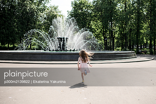 Little girl running towards a fountain - p300m2139822 by Ekaterina Yakunina