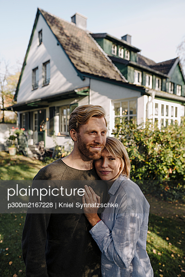 Smiling couple standing in front of their home - p300m2167228 von Kniel Synnatzschke