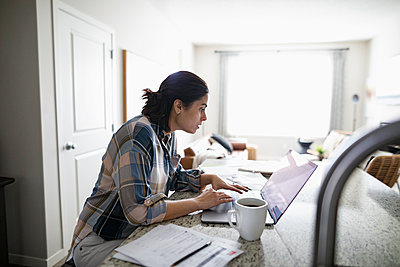 Woman working from home at laptop in kitchen - p1192m2088589 by Hero Images