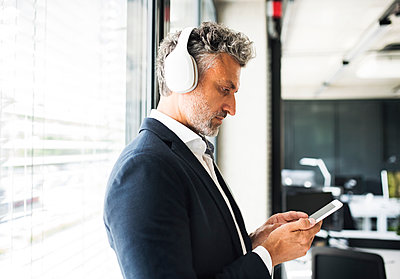 Mature businessman at the window in office with headphones and cell phone - p300m1536038 by HalfPoint